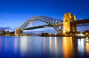 Sydney Harbour Bridge at twilight with reflection in the still water, clear blue sky, Australia.
