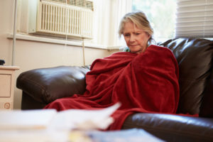 Senior Woman Trying To Keep Warm Under Blanket At Home Looking Off Camera
