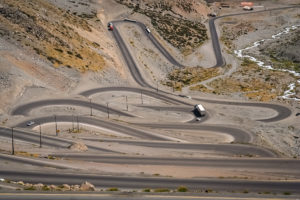 Cars trucks and lorries driving on the twisting and turning switchback road through high Andes in Chile, South America